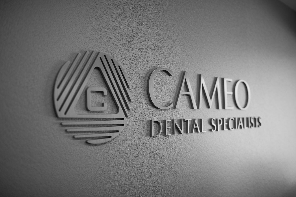 Doctor consulting a patient sitting in the dental chair at Cameo Dental Specialists