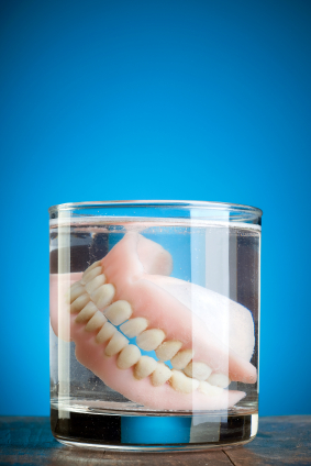 Dentures soaking in a glass full of water with blue background Cameo Dental Specialists, Chicago Periodontist